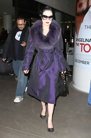 Dita rocks an iridescent purple trench coat with a large fur stole collar when arriving at LAX.
