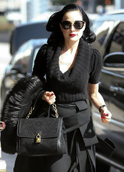 Dita Von Teese dressed down a detailed pencil skirt with a black cowl neck sweater.