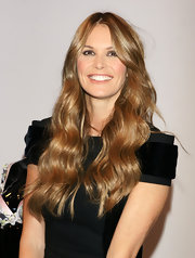 Elle's hair is styled with long relaxed waves. This style is ideal for her soft features and natural beauty.