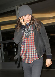 Ellen keeps warm at the airport in a gray knit beanie.