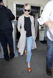 Emma Stone topped off her travel look with a nude duster coat.