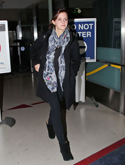 Emma Watson used a colorful scarf and hoop earrings to spice up a plain black pea coat.