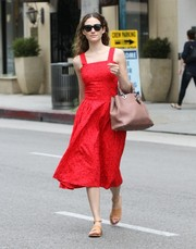 Emmy Rossum paired her lovely dress with a classic leather tote by Christian Dior.