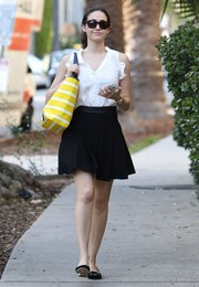 Emmy Rossum added a preppy touch to her look with a pleated black LaPina mini skirt.
