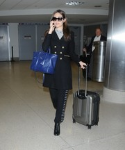 Emmy Rossum went for a military-chic airport look with this side-striped pants and gold-buttoned coat combo.
