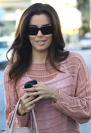 Eva Longoria left a hair salon with her tresses styled in long sleek layers.