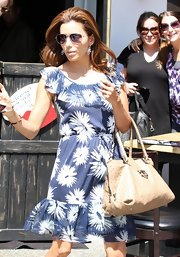 Eva paired her flower print day dress with a tan Ostrich satchel.