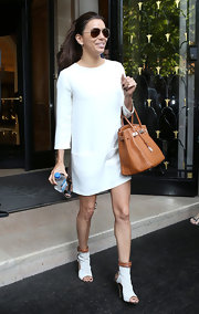 Eva Longoria paired her crisp white dress with white and tan cutout ankle boots.