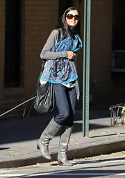 Famke Janssen looks ultra chic in gray leather knee high boots. A matching cardigan and blue printed scarf are the perfect additions to the street chic look.