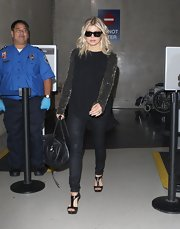 Fergie traveled in sheer style in a black top with embellished sleeves paired with black tights. She topped off her look with black leather strappy sandals.