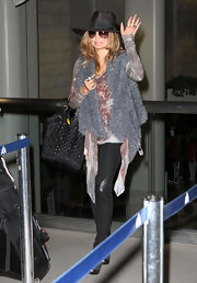 Fergie rocks the boho chic look carrying a stud embellished black tote. A furry vest keeps the singer's look decidedly on-trend.