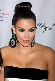 Kim Kardashian wore her hair in a super sleek bun at the Gabrielle's Angel Foundation ball. The elegant style allowed her to showcase some statement making earrings.