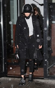 Bella Hadid teamed a black wool coat with ripped jeans for a night out in New York City.