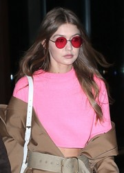 Gigi Hadid topped off her colorful ensemble with a pair of red shades.