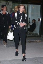 Gigi Hadid completed her casual outfit with black leather sneakers.