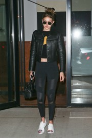 Gigi Hadid teamed a black leather jacket with a crop-top and a pair of leggings for a day out in New York City.