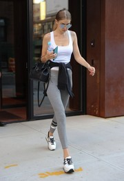 Gigi Hadid teamed her top with striped gray leggings by Sundry.