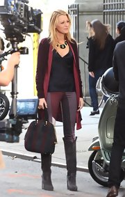 Blake Lively paired her burgundy, gray, and red striped outfit with a sumptuous matching suede bowler bag.