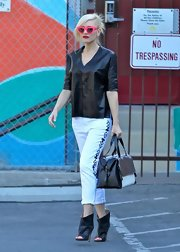 Gwen cuffed her white skinny jeans, which featured cool Aztec-inspired designs on the sides, for her on-the-go look.