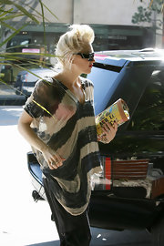 Gwen Stefani added some color to her neutral outfit via a printed L.A.M.B. clutch.