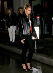 Hailey Baldwin was tough-glam in a boxy black leather jacket by Acne Studios while dining out at Catch.