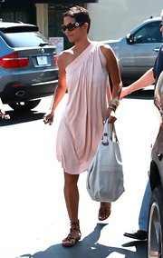 Another day of trying to escape the paparazzi all the whie lookin g stunning. Looking very greek goddess with white leather bag in hand, Halle greats her frenemies with a warm smile.