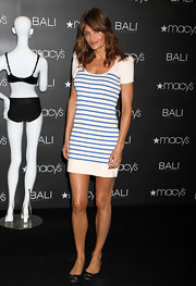 The model showed off her toned and tanned legs in a striped mini dress and a pair of metallic dress flats.