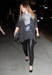 Hilary Duff dons classic black pumps with her trendy leather leggings. One of her signature scarves completes the casual chic look.