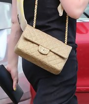 Hilary Duff paired her black maxi and head scarf with a gold shoulder bag while out walking in Beverly Hills.