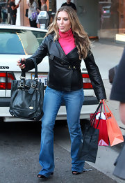 Brooke Mueller went shopping with a large black tote bag. The handbag features gold hardware and matched her leather jacket.