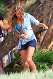 Indiana Evans used a blue linen button-down shirt as a cover-up while filming a beach scene.
