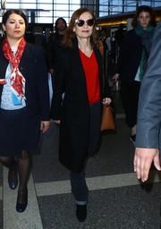 Isabelle Huppert teamed a black coat with a red V-neck sweater and jeans for her travel look.