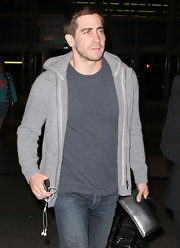 Jake wears a gray zip up hoodie over jeans a tee for this casual comfy look.