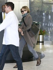 Jennifer Aniston stopped by a Beverly Hills spa wearing a long tan shawl-collar cardigan by Allsaints.