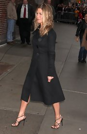 Jennifer's strappy black evening sandals looked sexy with her black calf-length trench coat. This minimalist style is a great staple shoe that can go with a variety of evening looks.