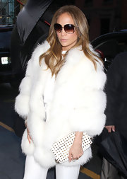 Jennifer Lopez toughened her uber glam winter white with a studded clutch.