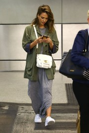 Jessica Alba took a flight to Miami wearing an oversized military jacket by Smythe over a gray maxi dress.