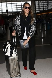 Jessica Alba traveled in styled in this silver paisley and floral-print jacket.