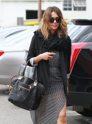Jessica Alba layered a slouchy black blazer over a print dress for a day at the office.