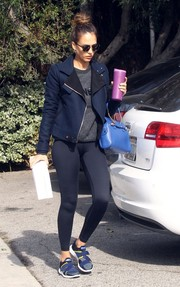 Jessica Alba toughened up her gym attire with a blue biker jacket.