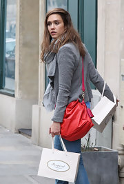 Jessica Alba livened up a gray jacket with a cherry red satchel with hot pink strap.