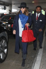 Jessica Alba landed at LAX looking cool in a navy wool coat, a patterned scarf, and a black hat.