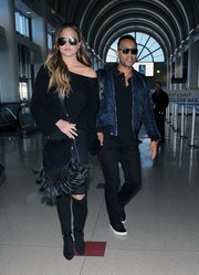 Chrissy Teigen looked oh-so-cool in a black Nili Lotan cashmere boatneck sweater teamed with ripped jeans while catching a flight.