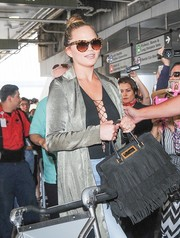 Chrissy Teigen arrived on a flight at LAX carrying a hippie-glam fringed suede tote.