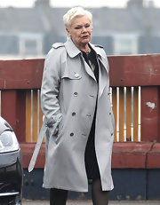 A double-breasted trenchcoat is a versatile piece that definitely spiced up Judi's all black ensemble!