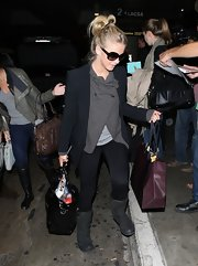 Julianne Hough kept warm by layering a navy blazer over a slouchy gray sweater at the airport.
