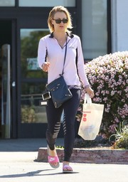 Kaley Cuoco styled her look with a black leather crossbody bag by Balenciaga.