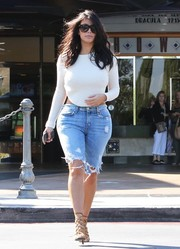 Kim Kardashian was grunge-chic in ripped jeans shorts and a crop-top while out on a date.