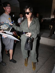 Kim Kardashian was tough-chic in a military-green jumpsuit by Vivienne Westwood while arriving on a flight at LAX.