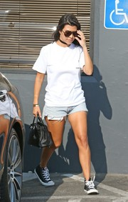 Kourtney Kardashian continued the easygoing vibe with a pair of denim cutoffs.